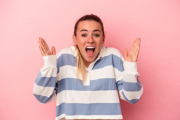 ピンクの背景に分離された若いロシアの女性はリラックスして幸せな笑い、首を伸ばして歯を見せています。