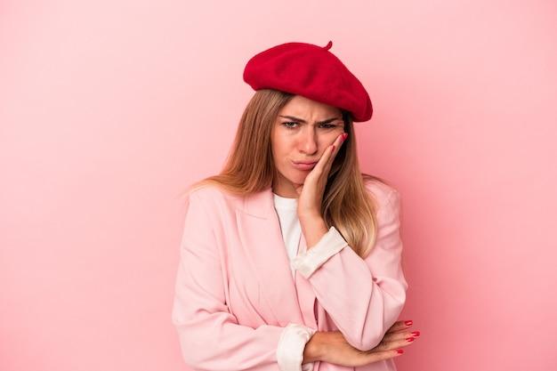 笑顔と手でハートの形を示すピンクの背景に分離された若いロシアの女性。