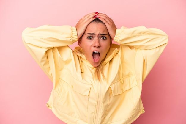 ピンクの背景に分離された若いロシアの女性は驚いてショックを受けました。