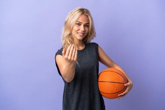 バスケットボールをし、来るジェスチャーをしている紫色の背景で隔離の若いロシアの女性