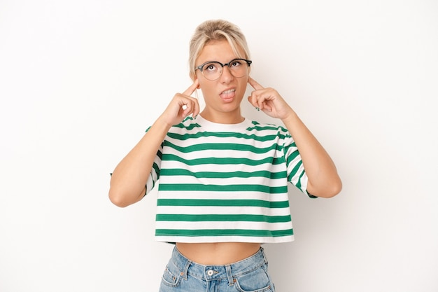 指で耳を覆う白い背景で隔離された若いロシアの女性は、大声で周囲によってストレスと必死になりました。