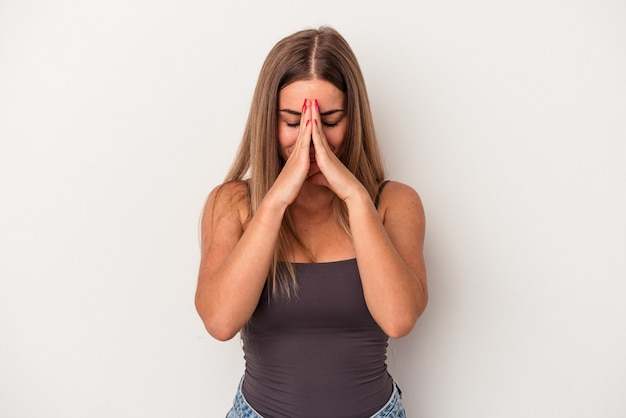 口の近くで祈って手をつないで白い背景で隔離の若いロシアの女性は、自信を持っています。