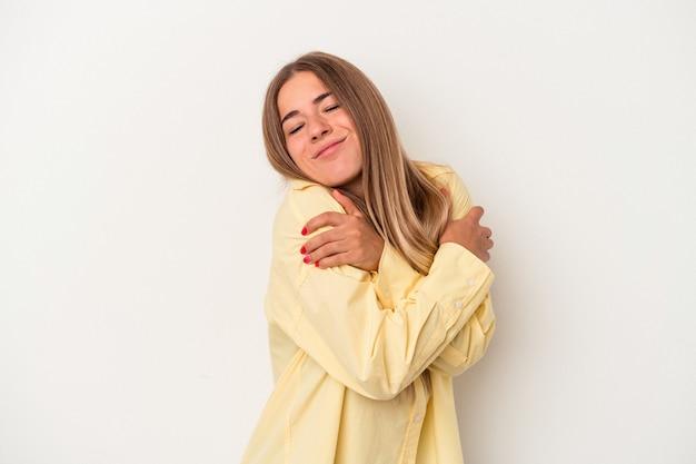白い背景で隔離の若いロシアの女性は、のんびりと幸せに笑って抱擁します。