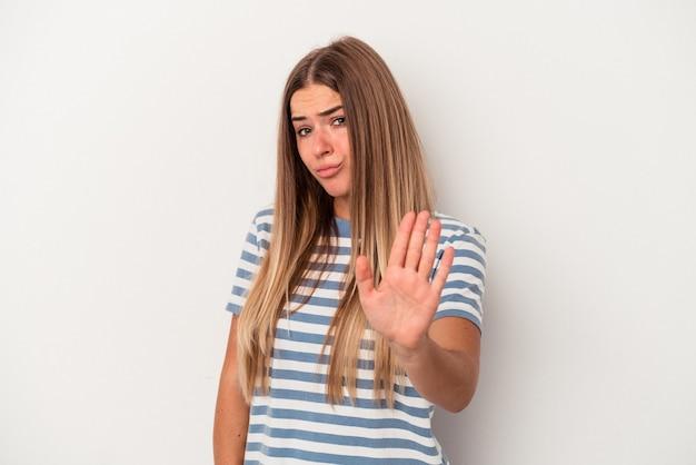 何かについて笑い、手で口を覆って、白い背景で隔離の若いロシアの女性。