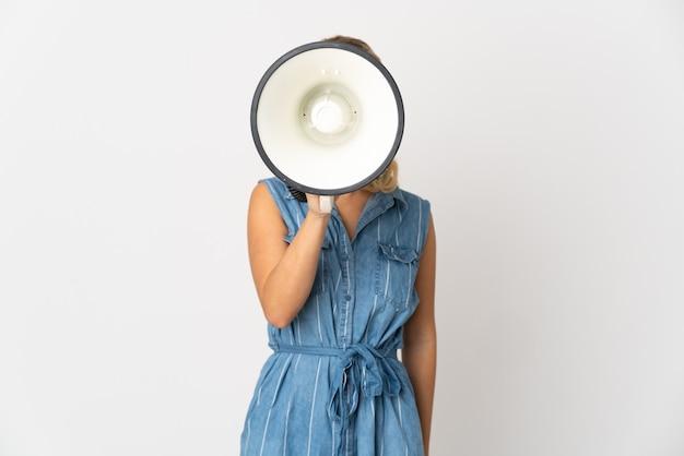 뭔가를 발표하는 확성기를 통해 외치는 흰색 배경에 고립 된 젊은 러시아 여자