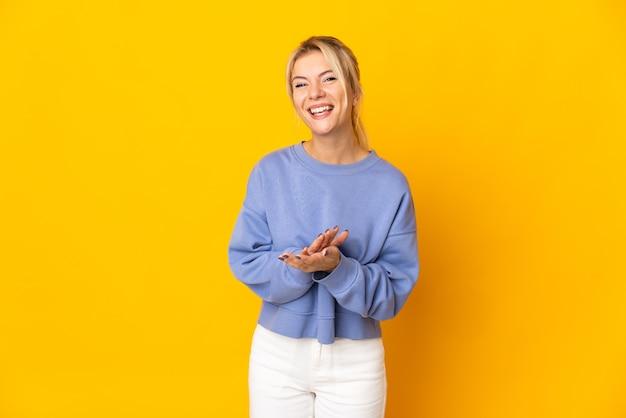 Молодая россиянка изолирована на желтом фоне аплодирует после выступления на конференции