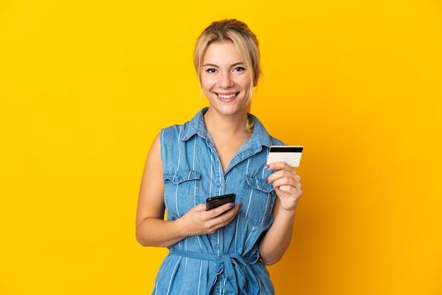 신용 카드로 모바일로 구매하는 노란색 배경에 고립 된 젊은 러시아 여자