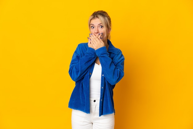 Молодая русская женщина изолирована на желтом фоне, прикрывая рот руками
