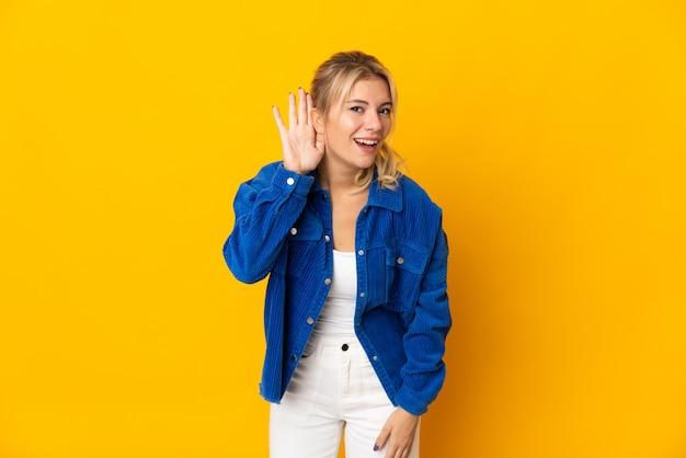 귀에 손을 넣어 뭔가를 듣고 노란색 배경에 고립 된 젊은 러시아 여자