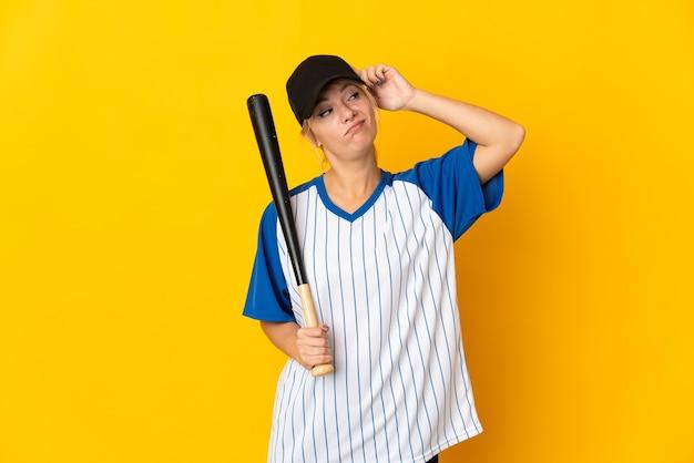 野球をしていて、混乱した表情に疑問を持っている黄色の背景に孤立した若いロシアの女性