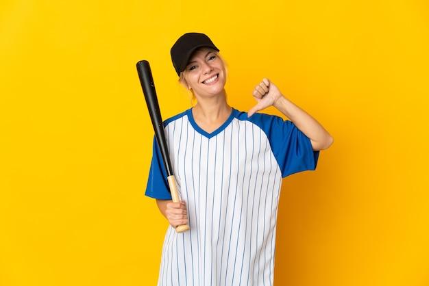 Молодая русская женщина изолирована на желтом фоне, играя в бейсбол и гордится