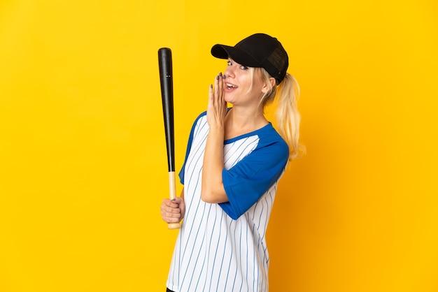 Молодая русская женщина изолирована на желтом фоне играет в бейсбол и что-то шепчет