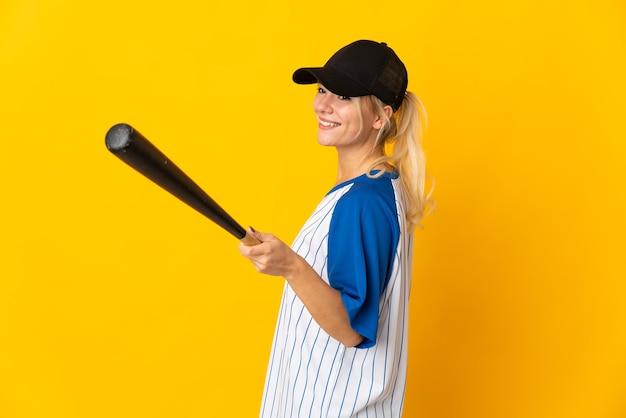 Молодая русская женщина изолирована на желтом фоне, играя в бейсбол