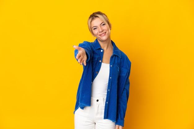 Молодая русская женщина изолирована на желтом фоне, пожимая руку для заключения хорошей сделки