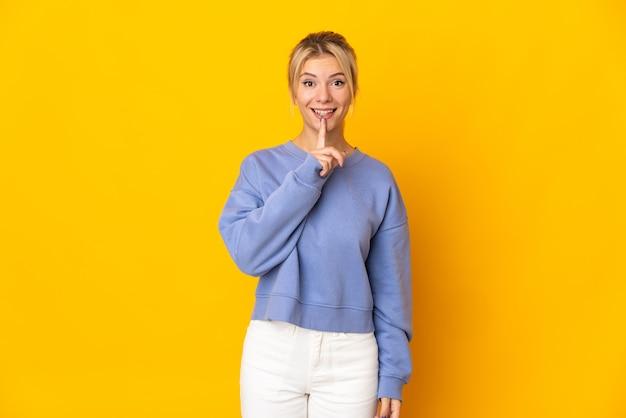입에 손가락을 넣어 침묵 제스처의 기호를 보여주는 노란색 배경에 고립 된 젊은 러시아 여자