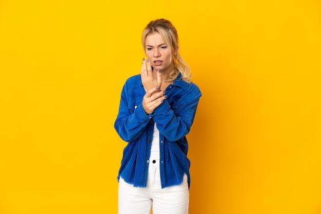 손에 통증을 앓고 노란색 배경에 고립 된 젊은 러시아 여자