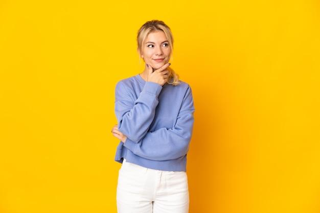 Молодая русская женщина изолирована на желтом фоне, думая об идее, глядя вверх