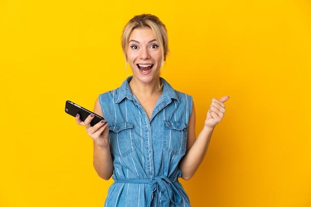 엄지 손가락을하는 동안 휴대 전화를 사용하여 노란색 배경에 고립 된 젊은 러시아 여자