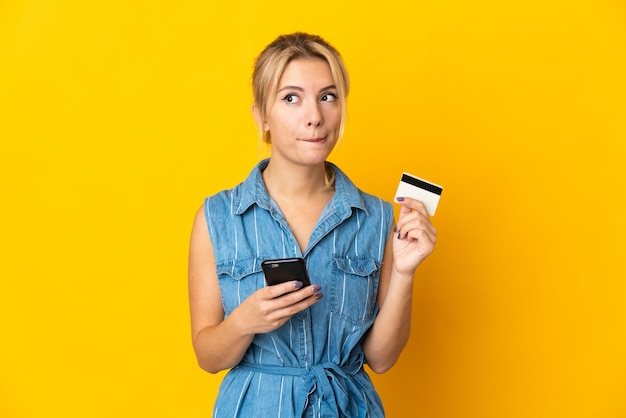 Молодая русская женщина изолирована на желтом, покупая с мобильного телефона с помощью кредитной карты, думая