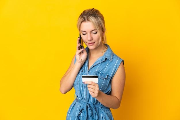 Молодая русская женщина изолирована на желтом, покупая с мобильного телефона с помощью кредитной карты