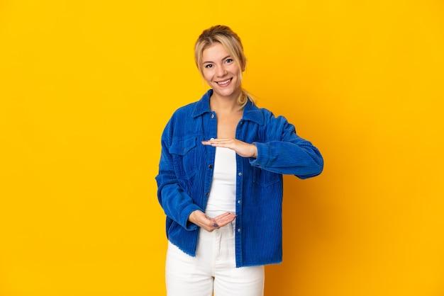 広告を挿入するために手のひらに架空のコピースペースを保持している黄色に分離された若いロシアの女性