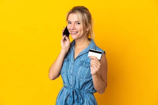 Молодая русская женщина изолирована на желтом, разговаривает по мобильному телефону и держит кредитную карту