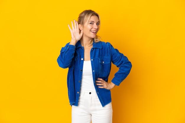 耳に手を置くことによって何かを聞いて黄色で孤立した若いロシアの女性