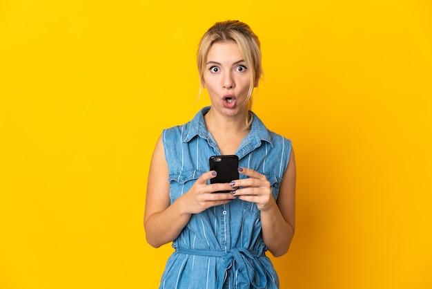 Молодая русская женщина изолирована на желтом, глядя в камеру, используя мобильный телефон с удивленным выражением лица