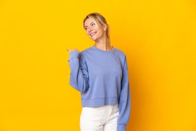 製品を提示する側を指している黄色で隔離の若いロシアの女性