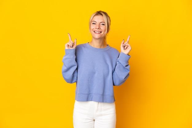 素晴らしいアイデアを指している黄色に孤立した若いロシアの女性