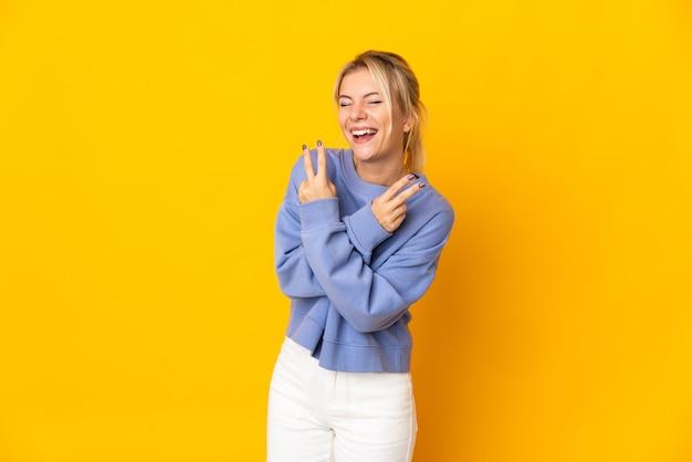 黄色の笑顔と勝利のサインを示して孤立した若いロシアの女性