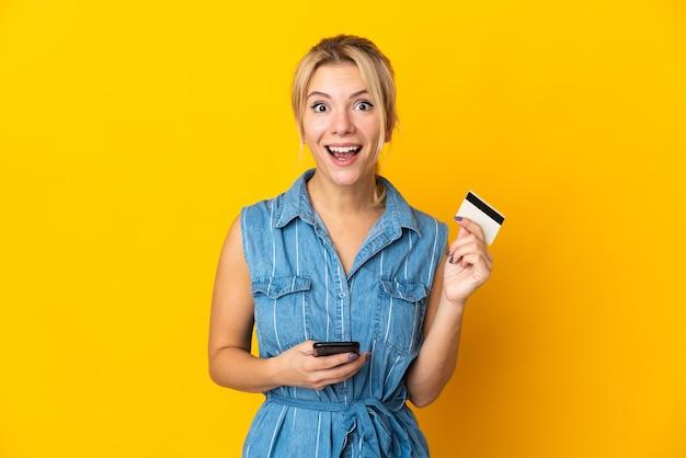 Молодая русская женщина изолирована на желтой стене, покупает с мобильного и держит кредитную карту с удивленным выражением лица