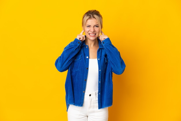 欲求不満と耳を覆っている黄色の壁に孤立した若いロシアの女性
