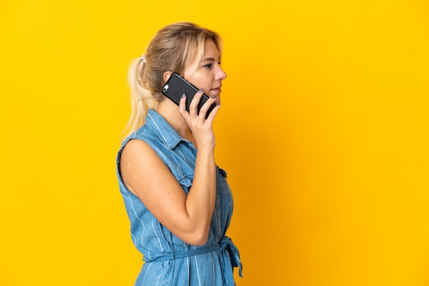 누군가와 휴대 전화로 대화를 유지하는 노란색 벽에 고립 된 젊은 러시아 여자