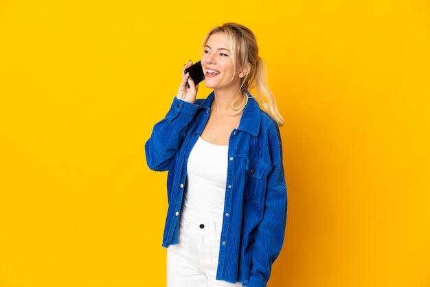 휴대 전화와 대화를 유지하는 노란색 벽에 고립 된 젊은 러시아 여자