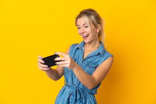 Молодая русская женщина изолирована на желтой стене, играя с мобильным телефоном