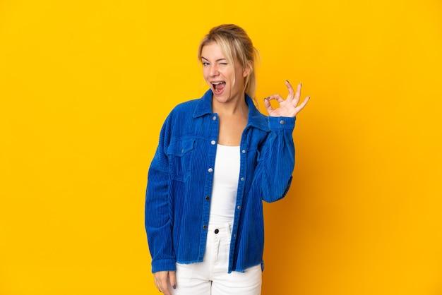 指でokサインを示す黄色の壁に分離された若いロシアの女性