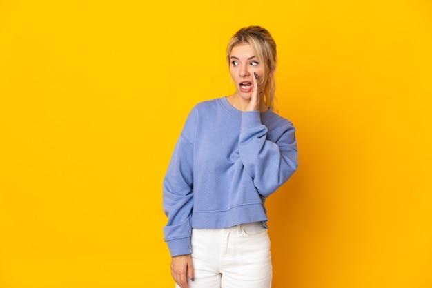 Молодая русская женщина изолирована на желтой стене, шепчет что-то с удивленным жестом, глядя в сторону