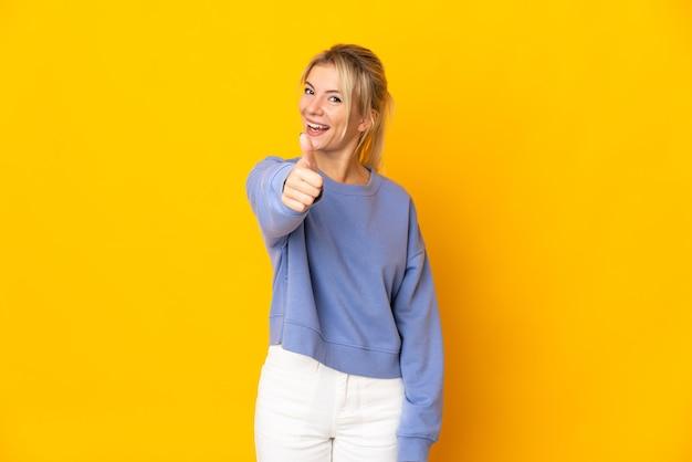 Молодая россиянка изолирована на желтом с большими пальцами вверх, потому что произошло что-то хорошее