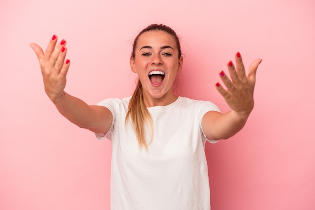 Young russian woman isolated on pink background celebrating a victory or success, he is surprised and shocked.