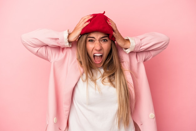 Young russian woman isolated on pink background crying, unhappy with something, agony and confusion concept.