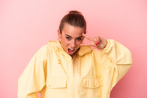 Young russian woman isolated on pink background dancing and having fun.