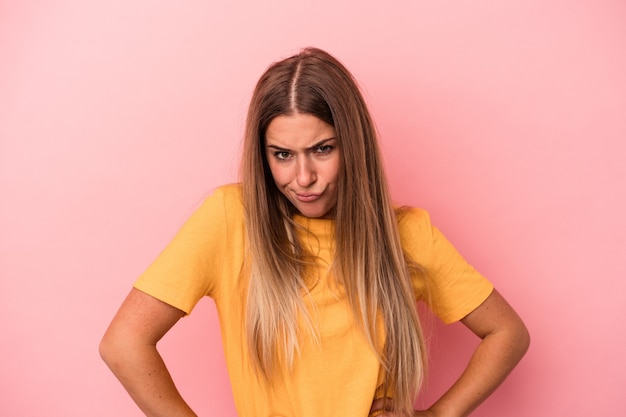 Young russian woman isolated on pink background has friendly expression, pressing palm to chest. love concept.