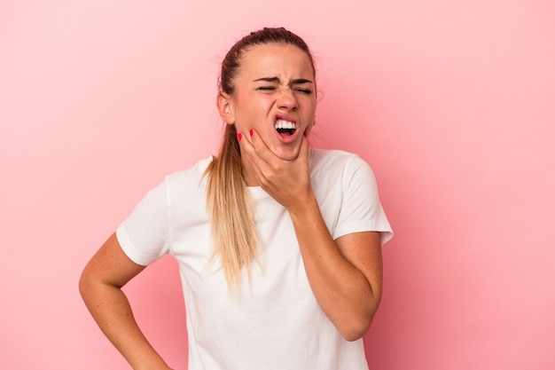 Young russian woman isolated on pink background having a strong teeth pain, molar ache.