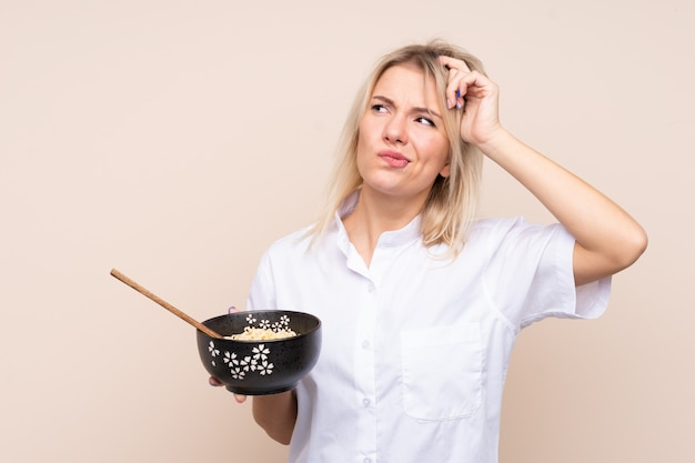 Young russian woman over isolated wall having doubts and with confuse face expression while holding a bowl of noodles with chopsticks