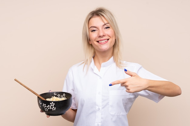 Young russian woman over isolated wall and pointing it while holding a bowl of noodles with chopsticks