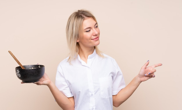 Young russian woman over isolated wall pointing to the side to present a product while holding a bowl of noodles with chopsticks