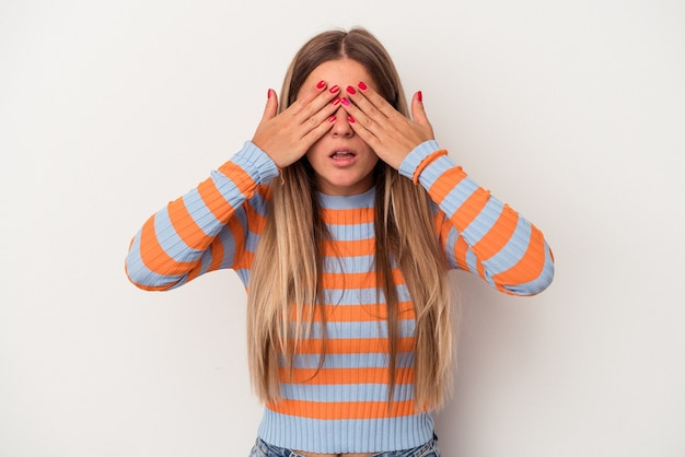 Young russian woman isolated on white background afraid covering eyes with hands.
