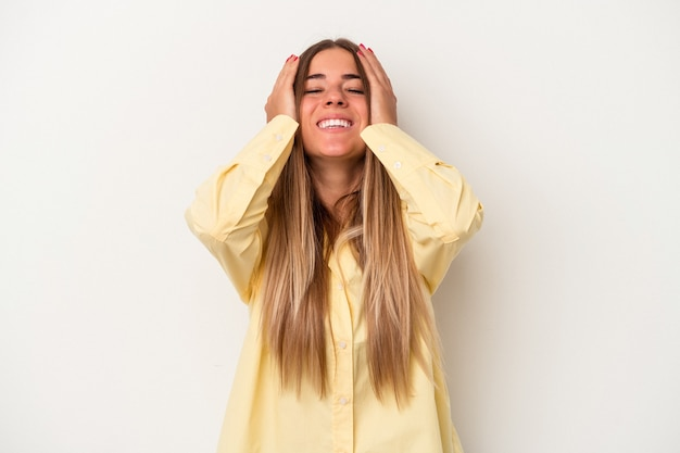 Young russian woman isolated on white background laughs joyfully keeping hands on head. happiness concept.