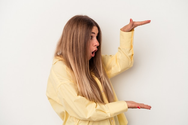 Young russian woman isolated on white background shocked and amazed holding a copy space between hands.